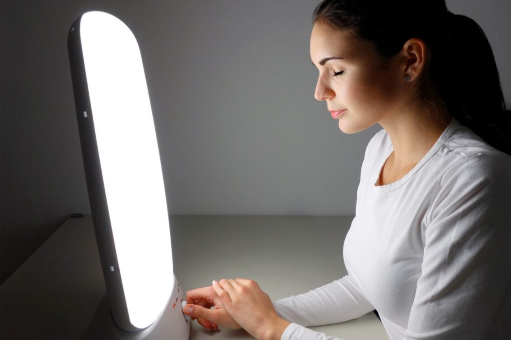 Young woman administering a light therapy agains winter depression